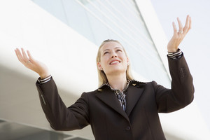 Businesswoman standing outdoors by building with hands out smiling