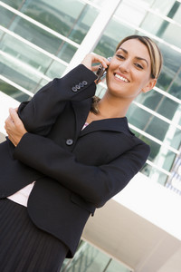 Businesswoman standing outdoors on cellular phone smiling