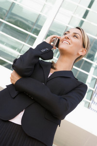 Businesswoman standing outdoors using cellular phone and smiling