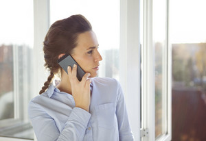 Businesswoman talking on mobile phone while standing by window and looking outside. Young caucasian female in office using phone.
