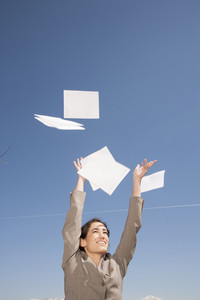 Businesswoman tossing papers