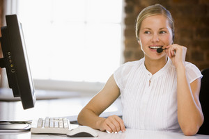 Businesswoman wearing headset in office smiling