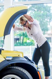 Businesswoman with car trouble looking under the car hood