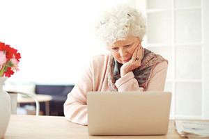 Busy senior woman at home reading something on her laptop