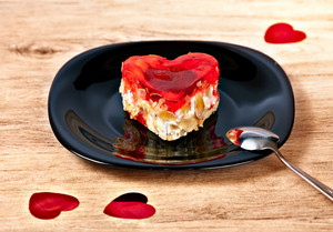Cake in the shape of heart served on a plate on wood table