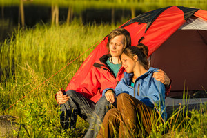 Camping couple hugging and enjoying the sunset