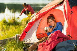 Camping girl sitting in tent drinking from pot