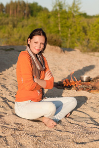 Camping happy woman relax on beach by  campfire
