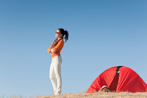 Camping happy woman standing outside tent on beach blue sky