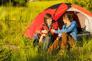 Camping teenagers drink beer outdoors sunset on the meadow