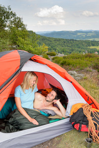 Camping young couple backpackers hugging in tent climbing gear sunset