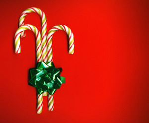 Candy Cane With Green Bow On Red Background