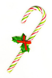 Candy Cane With Pretty Holly Leaves And Bow On White Background