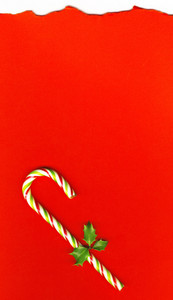 Candy Cane With Pretty Holly Leaves On Red Background