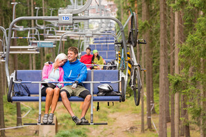 Carefree couple traveling by chair lift with bicycle