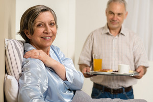 Caring senior man bringing breakfast to her sick wife