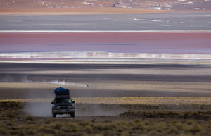Cars driving a dusty road through colorful flatland