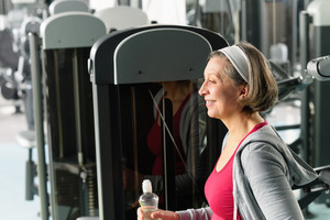 Senior woman relax at gym sitting by fitness machine