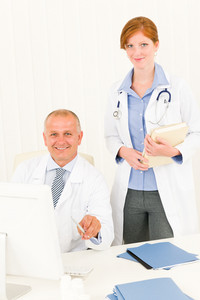 Medical senior doctor male with professional young female colleague office