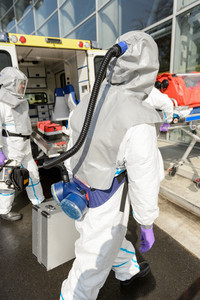 Hazardous material medical team with equipment walking towards contaminated building
