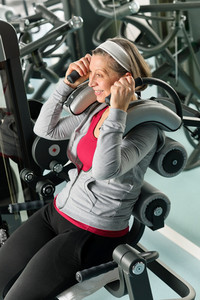 Fitness center senior woman exercise smiling on gym machine