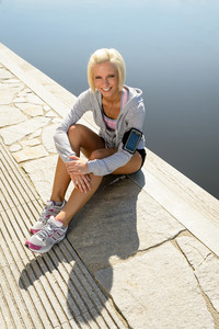 Sport woman relax on pier sitting by water summer day