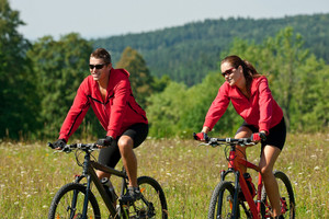 Young couple riding mountain bike in spring meadow on sunny day