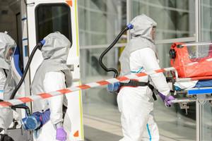 Hazardous material medical team with stretcher entering contaminated building