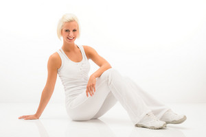 Attractive blonde woman relaxing during Pilates exercise on white background