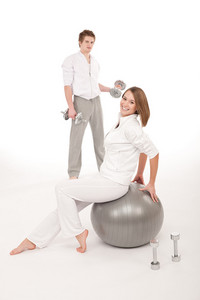 Young healthy couple training with weights and fitness ball on white