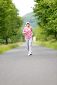 Jogging young fit woman running park road in sportswear tracksuit