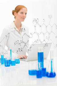Woman scientist in laboratory with laptop and chemical formula