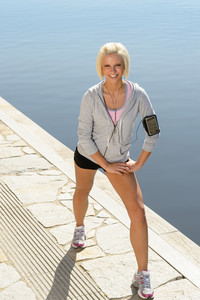 Sport blond woman stretching legs on a pier sunny day