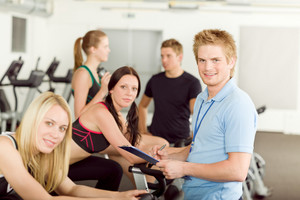 Young fitness instructor with gym people spinning or at cross-trainer