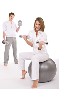 Fitness - Young couple exercise with weights and ball on white background