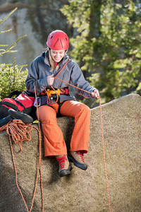 Active young woman prepare for rock climbing holding rope