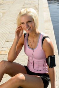 Sport young woman relax listen music by water pier sunny day