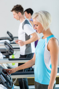 Woman set-up level on running belt at fitness center