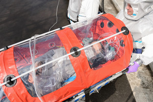 Biohazard medical team with sick patient in stretcher virus contamination