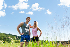 Sportive happy couple in countryside meadows blue summer sky