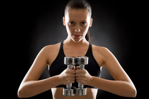 Portrait of sporty young woman holding dumbbells on black background