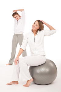 Fitness - Healthy couple stretching after training on white background