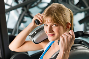 Young woman at gym exercise abdominal muscles on machine