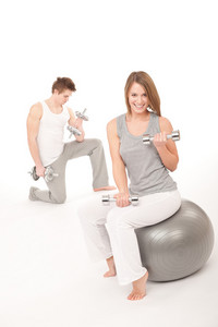 Fitness - Young healthy couple training with weights and ball on white background