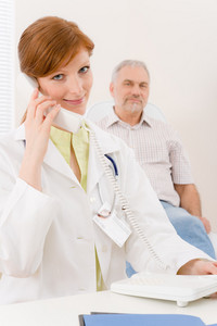 Doctor office - portrait female physician make phone call,senior patient in background