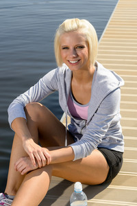 Smiling sport woman relax on pier water sunny day