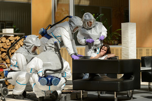 Biohazard medical team assisting contaminated female patient in lobby