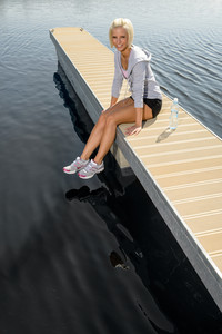 Smiling sport woman relax on pier lake sunny day