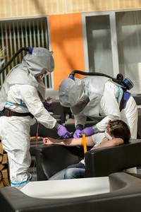 Biohazard medical team injecting unconscious contaminated female patient in lobby