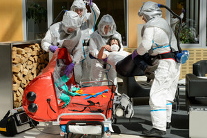 Biohazard medical team putting contaminated patient on stretcher in lobby